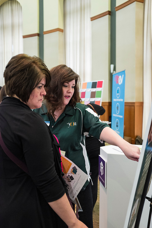 """Kelly Martin and UCM's Gabrielle Johnston look at a """"find the branding error"""" game during the CCN Expo in Walter Hall Rotunda on Wednesday, May 13, 2015.  Photo by Ohio University  /  Rob Hardin"""