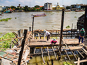 16 OCTOBER 2015 - BANGKOK, THAILAND: Demolition workers tear down houses in the Wat Kalayanamit neighborhood. The Chao Phraya River is in the background. Fifty-four homes around Wat Kalayanamit, a historic Buddhist temple on the Chao Phraya River in the Thonburi section of Bangkok, are being razed and the residents evicted to make way for new development at the temple. The abbot of the temple said he was evicting the residents, who have lived on the temple grounds for generations, because their homes are unsafe and because he wants to improve the temple grounds. The evictions are a part of a Bangkok trend, especially along the Chao Phraya River and BTS light rail lines. Low income people are being evicted from their long time homes to make way for urban renewal.    PHOTO BY JACK KURTZ