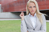 Portrait of confident businesswoman gesturing against office building