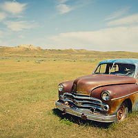 the old blue car parked in the short grass prairie of eastern and central montana, abandon car conservation photography - montana wild prairie