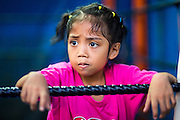 "18 DECEMBER 2104 - BANGKOK, THAILAND: A girl who wants to box watches a sparring session at the Kanisorn gym. The Kanisorn boxing gym is a small gym along the Wong Wian Yai - Samut Sakhon train tracks. Young people from the nearby communities come to the gym to learn Thai boxing. Muay Thai (Muai Thai) is a Thai fighting sport that uses stand-up striking along with various clinching techniques. It is sometimes known as ""the art of eight limbs"" because it is characterized by the combined use of fists, elbows, knees, shins, being associated with a good physical preparation that makes a full-contact fighter very efficient. Muay Thai became widespread internationally in the twentieth century, when practitioners defeated notable practitioners of other martial arts. A professional league is governed by the World Muay Thai Council. Muay Thai is frequently seen as a way out of poverty for young Thais and Muay Thai camps and schools are frequently crowded. Muay Thai professionals and champions are often celebrities in Thailand.     PHOTO BY JACK KURTZ"
