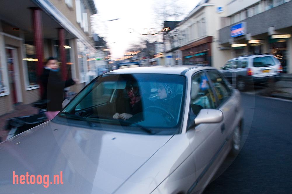 een moslima met hoofddoek rijdt in een auto terwijl zij een sigaret rookt.