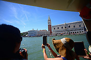 Tourists take photos from vaporetto, with Campanile di San Marco (St. Mark's bell tower) in view, Venice, Italy