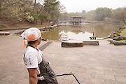 A rickshaw puller showing a well known pavillion in a lake near Nara Park.