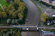 Nederland, Zuid-Holland, Goude, 23-10-2013; sprinter op spoorbrug over Gouwe / Gouwekanaal richting het centrum. Links park Wilhelminakade.<br /> Train on the railway bridge on the river Gouwe (Gouwe canal) in the city of Gouda.<br /> luchtfoto (toeslag op standaard tarieven);<br /> aerial photo (additional fee required);<br /> copyright foto/photo Siebe Swart.