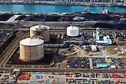 Nederland, Zuid-Holland, Maasvlakte, 23-05-2011; LNG-installatie van de Gasunie (LNG: Liquefied Natural Gas, vloeibaar aardgas); het vloeibare aardgas, de tank links (met betonnen beschermende buitenwand) bevatten een buffervoorraad vloeibaar aardgas. Als in extreme winteromstandigheden de vraag naar aardgas sterk toeneemt en de normale capaciteit bereikt is, kan er extra gas aan het netwerk geleverd worden: het vloeibare gas wordt opgewarmd tot het weer gasvormig is. Omdat bij het vloeibaar maken van het aardgas de natuurlijk aanwezige stikstof zich afscheid, wordt dit ook - vloeibaar - opgeslagen (in de witte tank, met logo). Als het aardgas weer gasvormig gemaakt is wordt ook weer de stikstof toegevoegd..LNG installation and the buffer stock liquid natural gas (liquefied natural gas, LNG) in the Port of Rotterdam..luchtfoto (toeslag), aerial photo (additional fee required).copyright foto/photo Siebe Swart