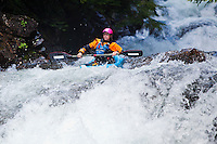 A woman running one of the drops on the middle fork of the Snoqualmie river, Washington, USA.