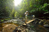 A tourist pauses to snap a picture from a wooden bridge crossing the Pargo river in the rainforest of Corcovado National Park, the largest park in Costa Rica.