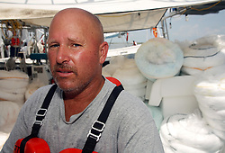 06 June 2010. Barataria Bay to Grand Isle, Jefferson/Lafourche Parish, Louisiana. <br /> Jimmy Terrebonne Snr sits surrounded by oil boom on his boat in Barataria Bay. The shrimp boater should be sweeping the waters for up to $5,000 worth of beautiful Gulf shrimp a day but the fishing grounds are all closed. Instead he is making around $1,000 a day for oil for BP contractors instead, a fraction of what he would ordinarily be making with bills mounting at home. The fisherman does not have a fixed contract within BP and does not know when BP will stop hiring him. He does however know that his life will never be the same again. The ecological and economic impact of BP's oil spill is devastating to the region. Oil from the Deepwater Horizon catastrophe is evading booms laid out to stop it thanks in part to the dispersants which means the oil travels at every depth of the Gulf and washes ashore wherever the current carries it. The Louisiana wetlands produce over 30% of America's seafood and are the most fertile of their kind in the world.<br /> Photo; Charlie Varley/varleypix.com