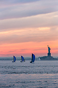 The vew of New York Harbor from behind Fariway Markete in Red Hook—a fleet of J 80s pass the Statue of Liberty while returning to the harbor, their spinnakers set.