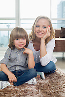 Portrait of happy mother sitting with boy on rug in living room