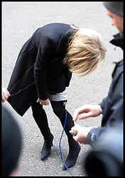 ITV news presenter Mary Nightingale uses gaffa tape to strap her mic onto her leg while reporting on the  death of Baroness Thatcher, outside No10 Downing Street, London, UK, Monday 8 April, 2013. Photo By Andrew Parsons / i-lmages.