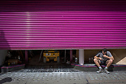 A workman on his cigarette break crouches beneath a half-lowered purple shutter, on 31st July 2017, in Oxford Street, London, England.