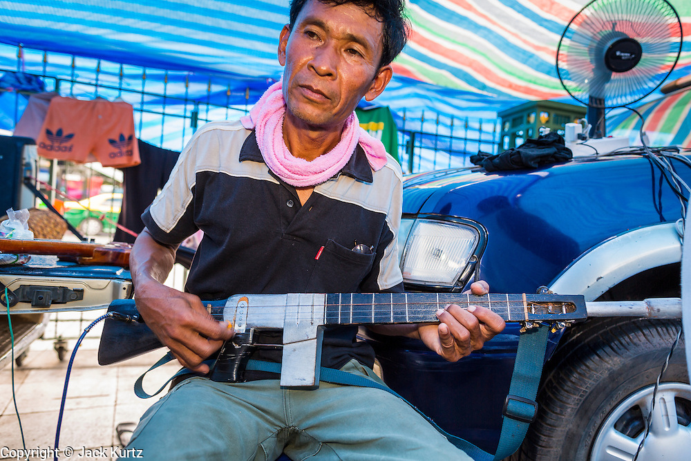 11 MAY 2013 - BANGKOK, THAILAND:  A Yellow Shirt protester with a guitar shaped like an assault rifle performs in the Yellow Shirt encampment on Sanam Luang. A faction of the Yellow Shirts are camping at Sanam Luang, the royal parade ground in front of the Grand Palace, to show support for the Thai monarchy and the Thai Constitutional Court. The court has become a flash point in Thai politics because Red Shirts claim the court is biased against them and have been protesting against the court, calling for the justices' ouster and replacement with justices more open to the Red Shirts. The Yellow Shirt protest at Sanam Luang is calling for the Justices to remain on the court.    PHOTO BY JACK KURTZ