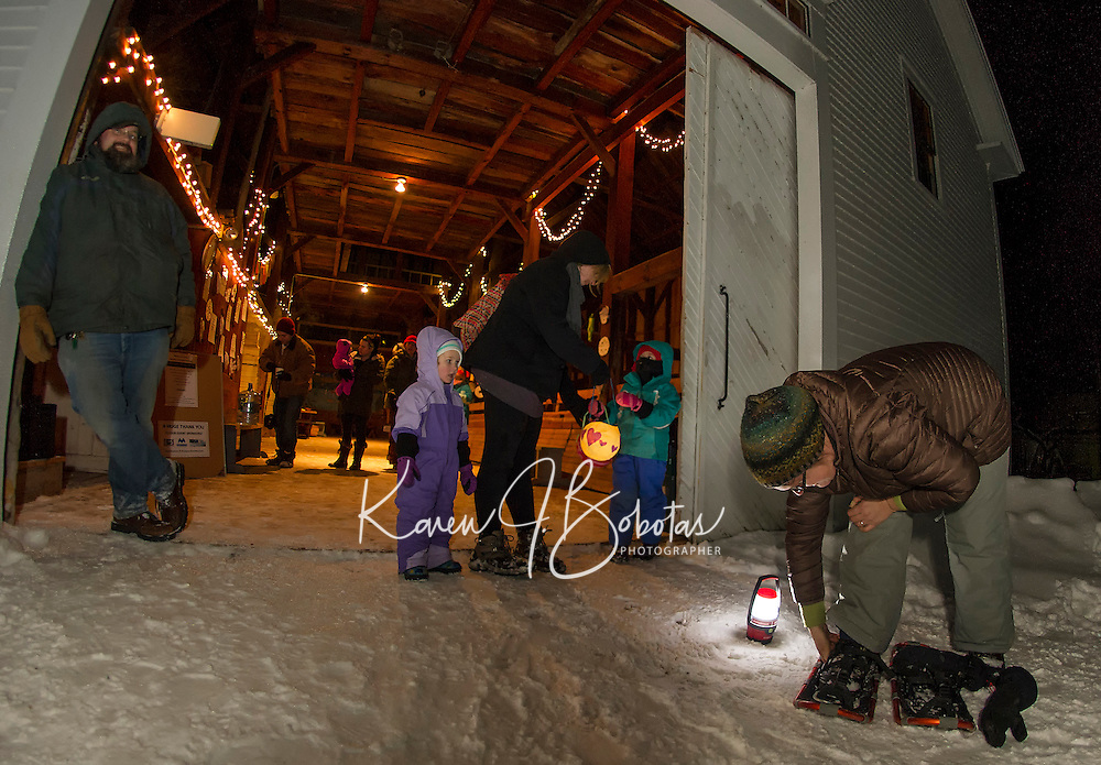 Dietrick, Maya, Susan and Chloe Bosk ready their lanterns while Sarah Dunham-Militois straps on her snowshoes for the adventure walk during the Lantern Festival at Prescott Farm on Saturday evening. (Karen Bobotas/for the Laconia Daily Sun)