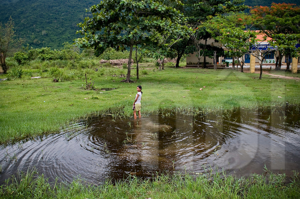 A young vietnamese girl wades in a pond of Ninh Hoa countryside area. Vietnam, Asia