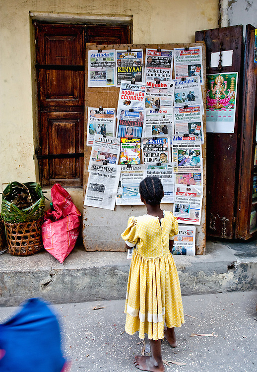stonetown street, young girl in a yellow dress reading placards on a news stand.