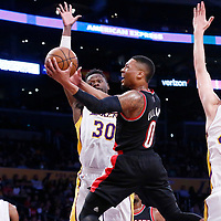 26 March 2016: Portland Trail Blazers guard Damian Lillard (0) goes for the layup past Los Angeles Lakers forward Julius Randle (30) during the Portland Trail Blazers 97-81 victory over the Los Angeles Lakers, at the Staples Center, Los Angeles, California, USA.