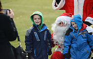 NEWTOWN, PA -  DECEMBER 7:  Jimmy McGinty (L), 6 and Brian McGinty (R), 5 pose for photos with Santa (played by fireman Justin Lewis) at Santa's annual Newtown Township Candy Cane hunt December 7, 2013 in Newtown, Pennsylvania. (Photo by William Thomas Cain/Cain Images)