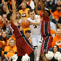 Oregon State's Tres Tinkle, center, tries to jump between Stanford's Dorian Pickens, left, and Marcus Sheffield in the second half of an NCAA college basketball game, in Corvallis, Ore., on Wednesday, Jan. 6, 2016. Stanford won 78-72. AP Photo/Timothy J. Gonzalez)