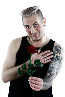 studio shot romantic blushing heart shy man  with tatoos and piercing holding a rose