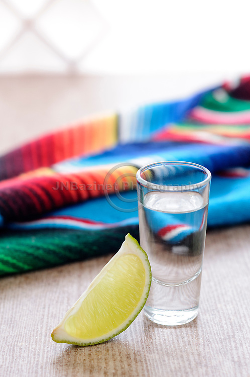 Tequila shot with lime wedge and mexican blanket