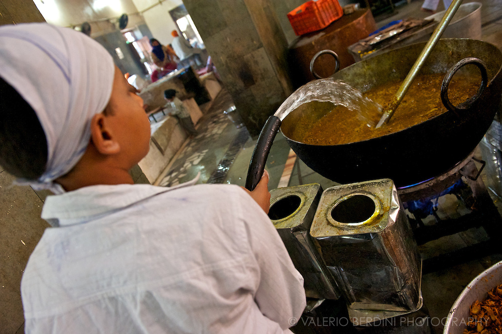 A child uses a water pipe to dilute a vegetable curry. All food served in the Langar is strictly vegetarian following Sikhs rules.