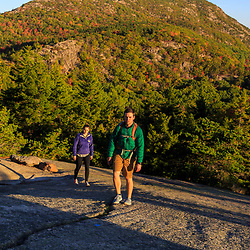 """A young couple hiking on """"The Beehive"""" in fall in Maine's Acadia National Park.`"""