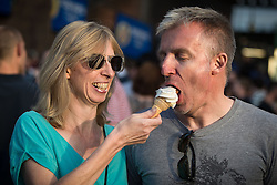 """© Licensed to London News Pictures . 04/07/2015 . Manchester , UK . A couple share an ice cream in the sunshine at the Castlefield Bowl as part of the """" Summer in the City """" festival in Manchester. Photo credit : Joel Goodman/LNP"""