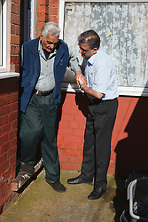 Son helping elderly south Asian father down step.