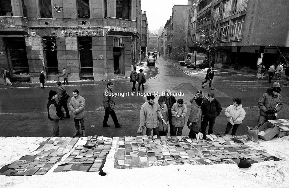 Sarajevans browse among books for sale spread out on a tarp laid over the snow during the final days of the siege of the city, Sarajevo, Bosnia and Herzegovina, February 1996. PHOTO BY ROGER RICHARDS