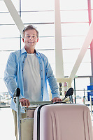 Portrait of mature attractive man pushing cart with his suitcase for check in at airport