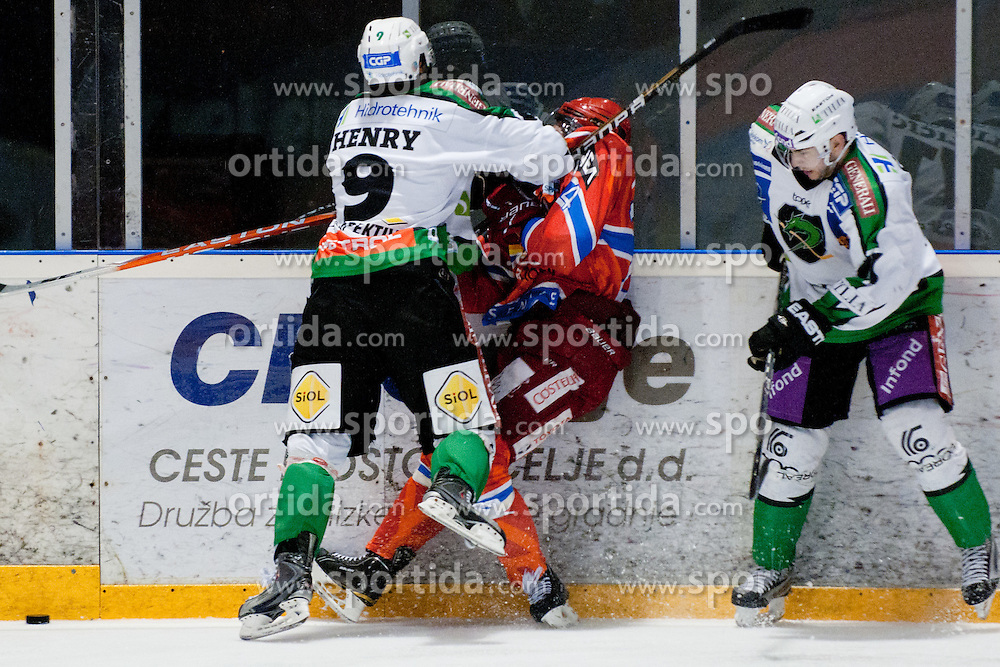 Burke Henry of HDD Tilia Olimpija hits Rok Ticar of HK Acroni Jesenice during ice-hockey match between HK Acroni Jesenice and HDD Tilia Olimpija in fourth game of Final at Slovenian National League, on April 8, 2011 at Dvorana Podmezaklja, Jesenice, Slovenia. (Photo By Matic Klansek Velej / Sportida.com)