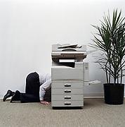 Businessman kneeling beside photocopier, side view