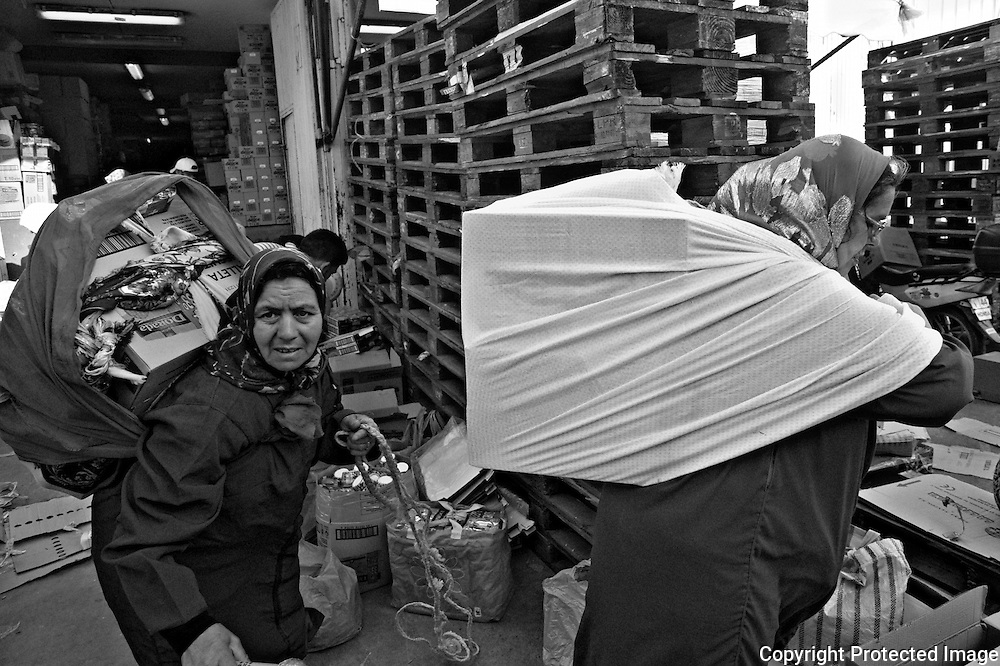 CEUTA, SPAIN - JUNE 27, 2010 : Outside of a warehouse two women are ready to go to  the pedestrian cross border of El Biutz   . Thousands  of people are involved in transporting smuggled goods from Ceuta (an Spanish enclave on the North African coast) to Morocco, it is estimated that every day enter 10.000 porters, mostly women, that it make between three and five trips to Morocco with all types of products purchased on  the warehouse border area of Biutz in Ceuta, Spain .( Photo by Jordi Cami  )