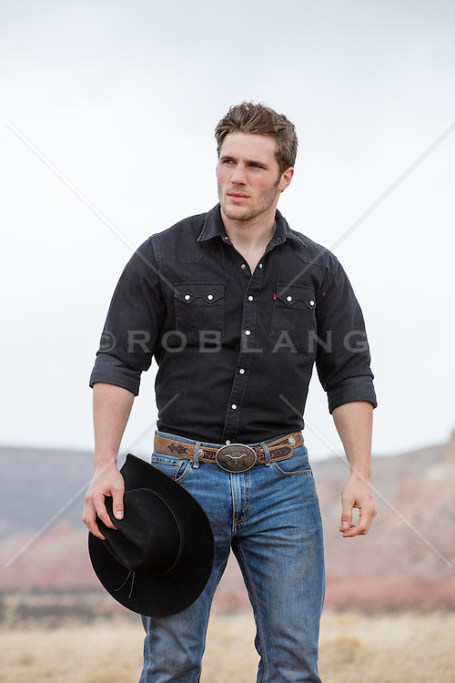 cowboy walking with his cowboy hat in his hand