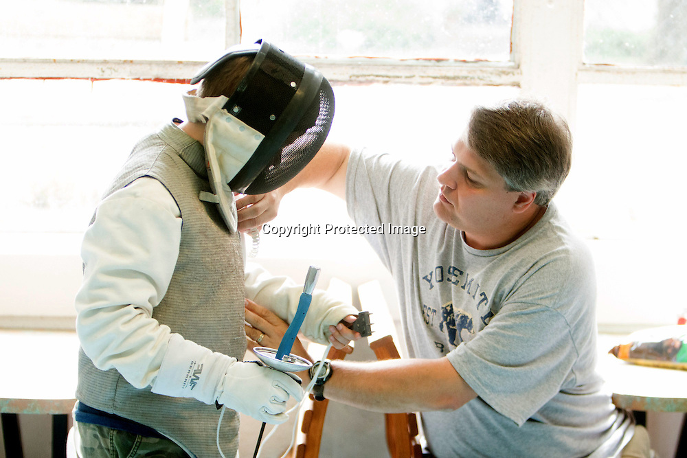 Jeff Waldyke helps his son Jason Waldyke, 11, prepare for a Cape Fear Fencing Association youth fencing tournament at Tileston Gym in Wilmington, N.C. Saturday May 31, 2014. (Jason A. Frizzelle)