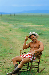 cowboy sitting in a rocking chair in his underwear and boots on a ranch