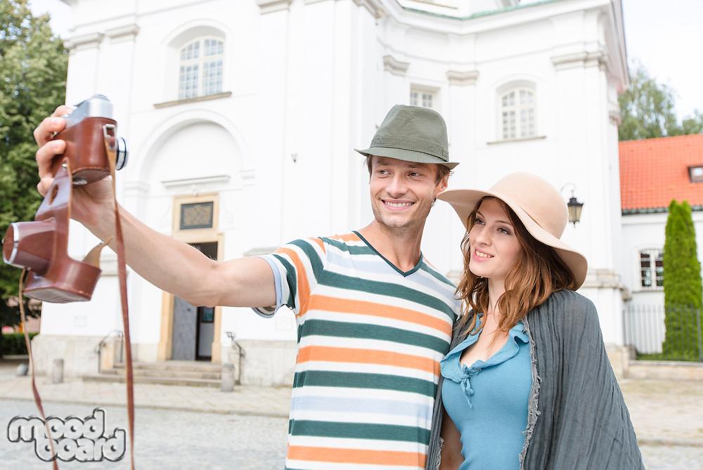 Tourist couple taking self portrait outside St. Casimir Church; Warsaw; Poland