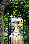 A decorative iron gate leading to the walled garden at Rousham House, Steeple Aston, Oxfordshire, UK