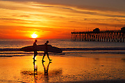 Longboard Surfers on the Beach at Low Tide by the San Clemente Pier