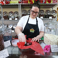 Christa Sheffield, an employee at Simply Sweet by Margarete, places chocolate truffles into a Valentine's box as she gets the store front stocked with sweets for Valentine's Day Tuesday in Tupelo.
