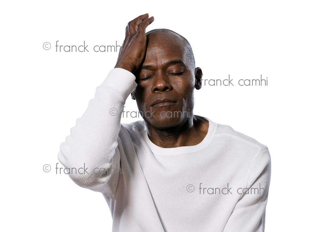 Close-up of a serious afro American man with headache in studio on white isolated background