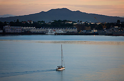 A sail boat heads out at dawn in Waitemata Harbour, with Rangitoto Island in the background, Auckland, New Zealand.