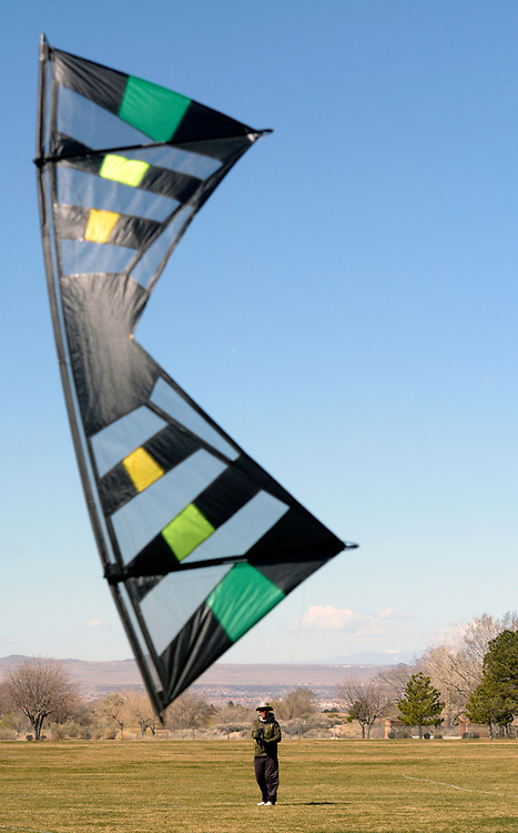 gbs030617h/ASEC -- David Costello of Albuquerque flies his Revolution kite in Arroyo Del Oso Park on Monday, March 6, 2017. Four, braided, fixed length, nylon strings control the sport kite which is made for high winds. One of his six revolution kites can fly in 25 to 30 mph sustained wind. (Greg Sorber/Albuquerque Journal)