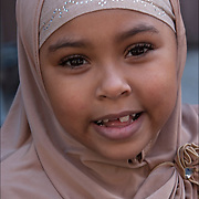 Portrait of smiling American Muslim girl missing front tooth wearing headscarf at the American Muslim Day Parade in New York City