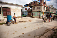 Man with hand cart and coche de caballos in Holguin, Cuba.