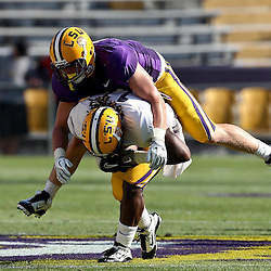 April 9, 2011; Baton Rouge, LA, USA;  LSU Tigers linebacker D.J. Welter (purple) tackles running back Spencer Ware (white) during the 2011 Spring Game at Tiger Stadium.   Mandatory Credit: Derick E. Hingle