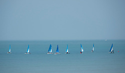 © Licensed to London News Pictures. 05/05/2018. Worthing, UK. A flotilla of sailing dinghies are seen through the heat haze in the sea off Worthing. Record temperatures are expected this bank holiday weekend. Photo credit: Peter Macdiarmid/LNP