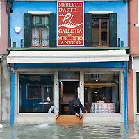 A shop  keeper tries to keep the water outside his shop in Burano, More than 59% of Venice was under water on Thursday, as the historic lagoon town was hit by exceptionally high tides. The sea level rose above 140cm overnight and was expected to remain above critical levels for about 15 hours.
